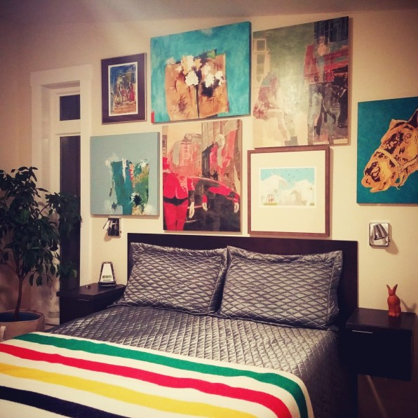art work grouped over bed by deborah nicholson lighting and interiors